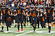 Gilmer players (from left) Blake Lynch, Chris Boyd, Chase Tate and McLane Carter carry the jersey of the late Desmond Pollard (8) and Gladewater's Nikalas Wisinger (68) out to the coin toss before their Class 4A Division II state championship game against West Orange-Stark on Friday at AT&T Stadium in Arlington. (Jeff Stapleton, ETSN.fm)