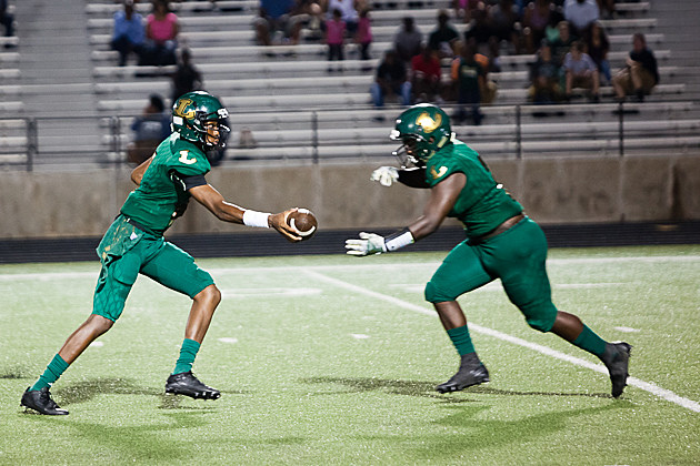Lobo's quarterback Gaylon Wiley hands the ball off to Kendrevian White
