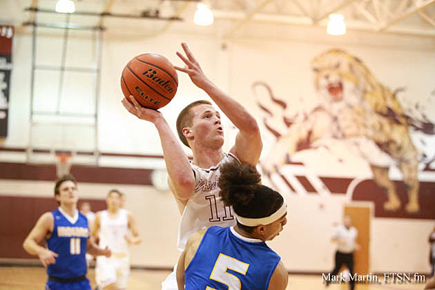 Whitehouse guard Zach Parker drives through Jacsonville's Cameron High for two points in the Wildcats' 57-54 victory Tuesday.